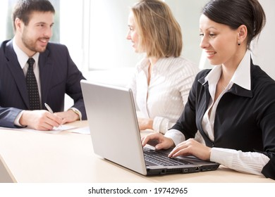 operates a laptop and her colleagues hold discussions