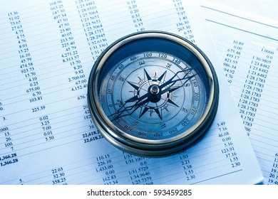Operating budget and vintage compass in closeup