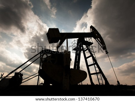 Operating oil and gas well contour, outlined on sky with storm clouds