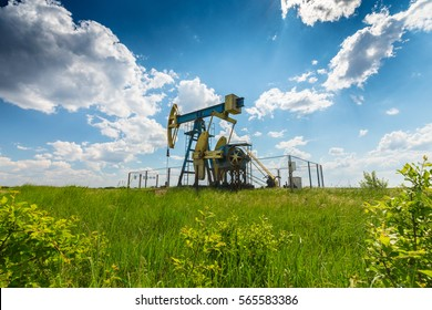 Operating oil and gas well in European oil field, profiled on blue sky with cumulus clouds, in spring