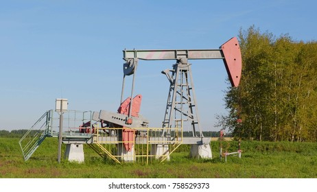 Operating oil and gas well in oil field, profiled against the blue sky.