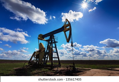 Operating oil and gas well profiled on bright sky with clouds