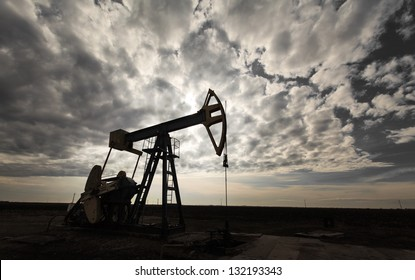 Operating oil well profiled on dramatic cloudy sky, in active oilfield