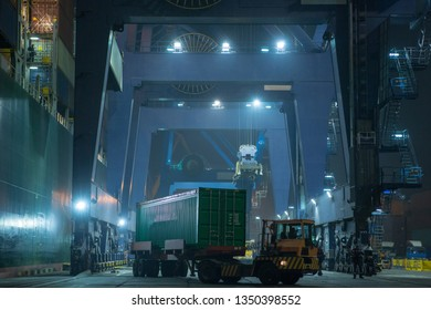 operation of container terminal at night. Unloading container ship at night. Mooring cranes unload container ship at night