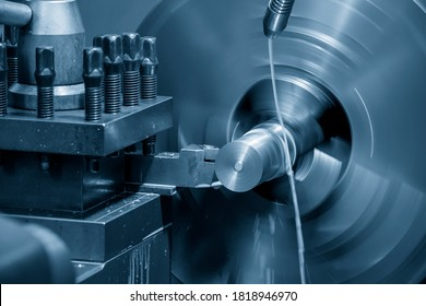 The operation of lathe machine cutting the metal shaft parts with the cutting tools. The metalworking process by turning machine.