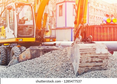 Operation of Wheel loader excavator for unloading crushed stone during the repair of city utilities and road works. Housing and communal services. Close up details of industrial construction site