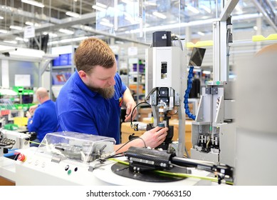 operator assembles machine in a factory - production of switch cabinets for industrial plant
