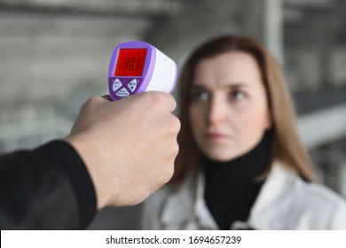 Operator-Check-Fieber durch den digitalen Thermometer Besucher an der Informationszähler zum Scannen und Schutz vor Coronavirus COVID-19.