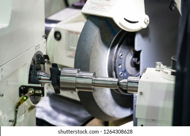 operator grinding and inspection high precision automotive part, high precision universal grinding machine, precision part manufacturing