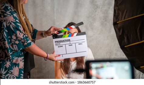 Operator holding clapperboard during the production of short film inside a studio with young actress on stage. Focus on the clapperboard and blur effect on the monitor and model.