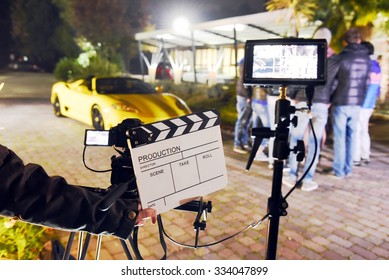 Operator holding clapperboard during the production of short film outdoor in the night with sportive yellow car and actor on stage. Focus on the clapperboard and monitors