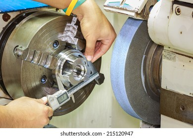 operator measuring cnc grinding part by vernier