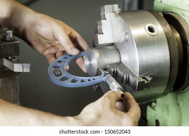 Operator measuring dimensions with a micrometer on a milling machine