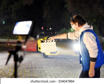 Operator od Director holding clapperboard during the production of movie film outdoor in the night with sportive yellow car in the background.