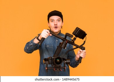 An operator with an open mouth is surprised when something shot on a dslr camera on an orange background. A young videographer using stabilization for a camera. Close-up portrait