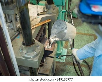 Operator pouring aluminum molten in to high precision casting mold, Alunimun foundry process manufacturing, pouring high temperature aluminum molten