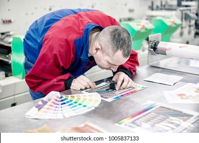 Operator in printing factory control colours with magnifying glass. Worker next to the printing machine check the print quality. Print quality control check.