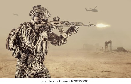 Operator of Russian special operations forces with kalashnikov assault rifle, military backpack and combat helmet shooting a weapon in the desert in Syria. Ancient ruins and helicopters