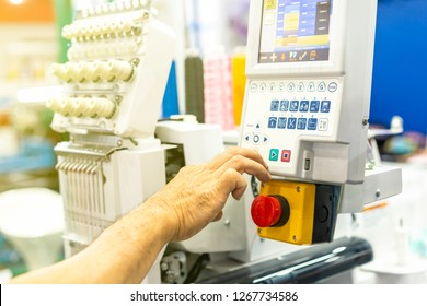 Operator or tailor working on control panel of modern and automatic high technology sewing or embroidery machine for textile - clothing apparel making manufacturing process in industrial