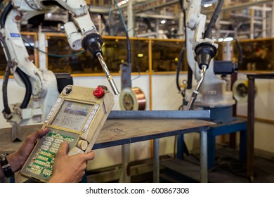 Operator is teaching robot for new program in car factory