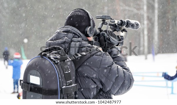 Operator with a video camera at work. Winter. Snow.