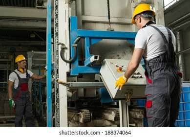 Operator wearing safety hat behind control panel on a factory