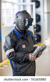 operator of the welding machine in the mask with remote control panel