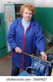 Operator woman-engineer  in machine room (elevator) check the mechanical equipment.