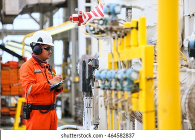 Operator or worker recording operation data of oil and gas process at production plant, Offshore oil and gas industry in the sea or gulf, Operator monitor production process and routine daily record.
