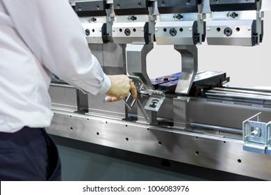 Operator working cut and bending metal sheet by high precision metal sheet bending machine,  control metal sheet bending machine in factory