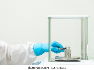 The operator's hand is holding stainless steel calibration weight to place on the analytical balance pan for the calibration test, concept of quality control laboratory in pharmaceutical industry.
