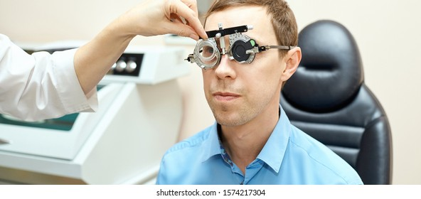 ophthalmologist doctor in exam optician laboratory with male patient. Men eye care medical diagnostic. Eyelid treatment.