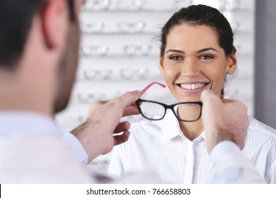 an ophthalmologist doing a visual examination for a customer at an optical center. Try the spectacles to the patient. Concept of: medical examination, assistance, optics and customer care.