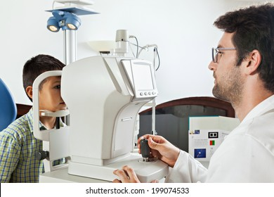 Ophthalmologist In Exam Room With Little Boy Sitting In Chair Looking Into Eye Test Machine