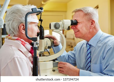 Ophthalmologist examing cornea of senior woman with slit lamp