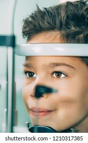 Ophthalmologist examining boy with slit lamp