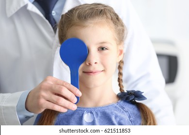 Ophthalmologist examining eyes of little girl in clinic