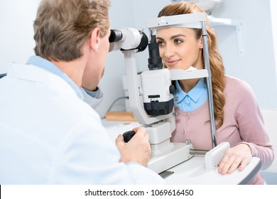 ophthalmologist examining female patient vision with slit lamp in clinic