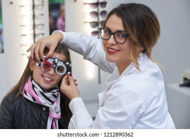 ophthalmologist examining little girl with modern equipment