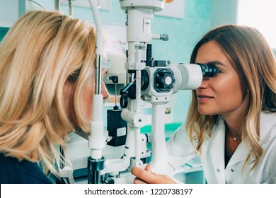 Ophthalmologist examining patient with slit lamp