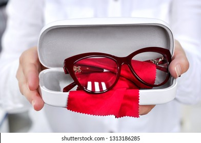 Ophthalmologist holding eyeglasses for a try out. Optometrist hands showing new plastic red eyeglasses with red microfiber on white case, at optician shop.Close-up view focused on glasses.