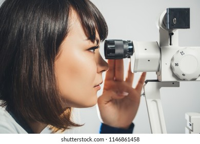 ophthalmologist Intern looks into eyepiece of eye-checking apparatus. Ophthalmology, hospital, medical examination.