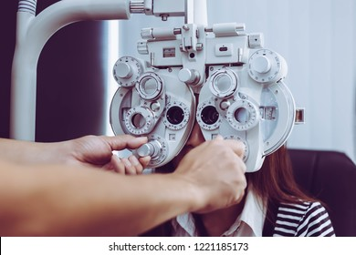 The ophthalmologist is measuring and finding customer's diopter that it is long sighted or shortsighted. Pretty woman needs new pair of glasses. Beautiful woman is checking her eyes by used phoroptor.