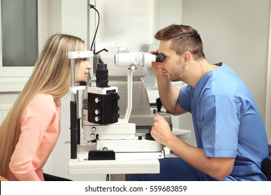 Ophthalmologist measuring intraocular pressure of young woman in clinic