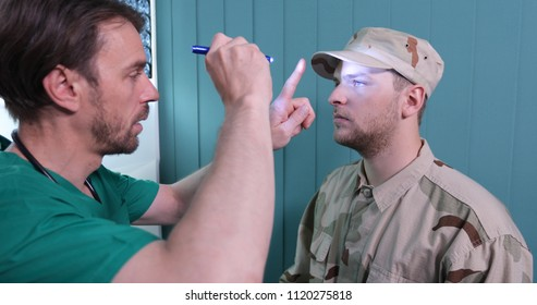 Ophthalmologist Medical Doctor Man Consulting Eye to a Soldier Patient with a Pen Light Instrument in Hospital Cabinet or Healthcare Centre Room