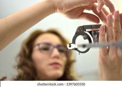 ophthalmologist optometrist optician with lens testing eye glasses frame, low depth of field