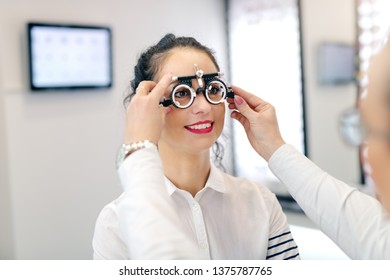 Ophthalmologist putting test glasses phoropter and checking eyesight of patient. Woman smiling and standing still.