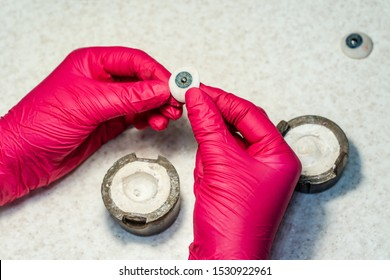 Ophthalmologist or surgeon holds in hand dressed in red gloves an eye, eyeball prosthesis. Concept photo for ocular prosthesis, diagnosis , treatment of ophtalmic diseases, surgical operations on eyes