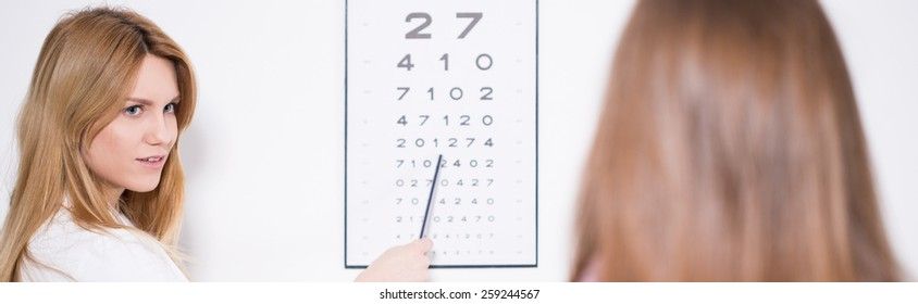 Ophthalmologist using Snellen chart to examine patient's vision