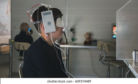 Ophthalmology clinic researching -boy with electrodes on the head looking to monitor - healthcare children's diagnostic
